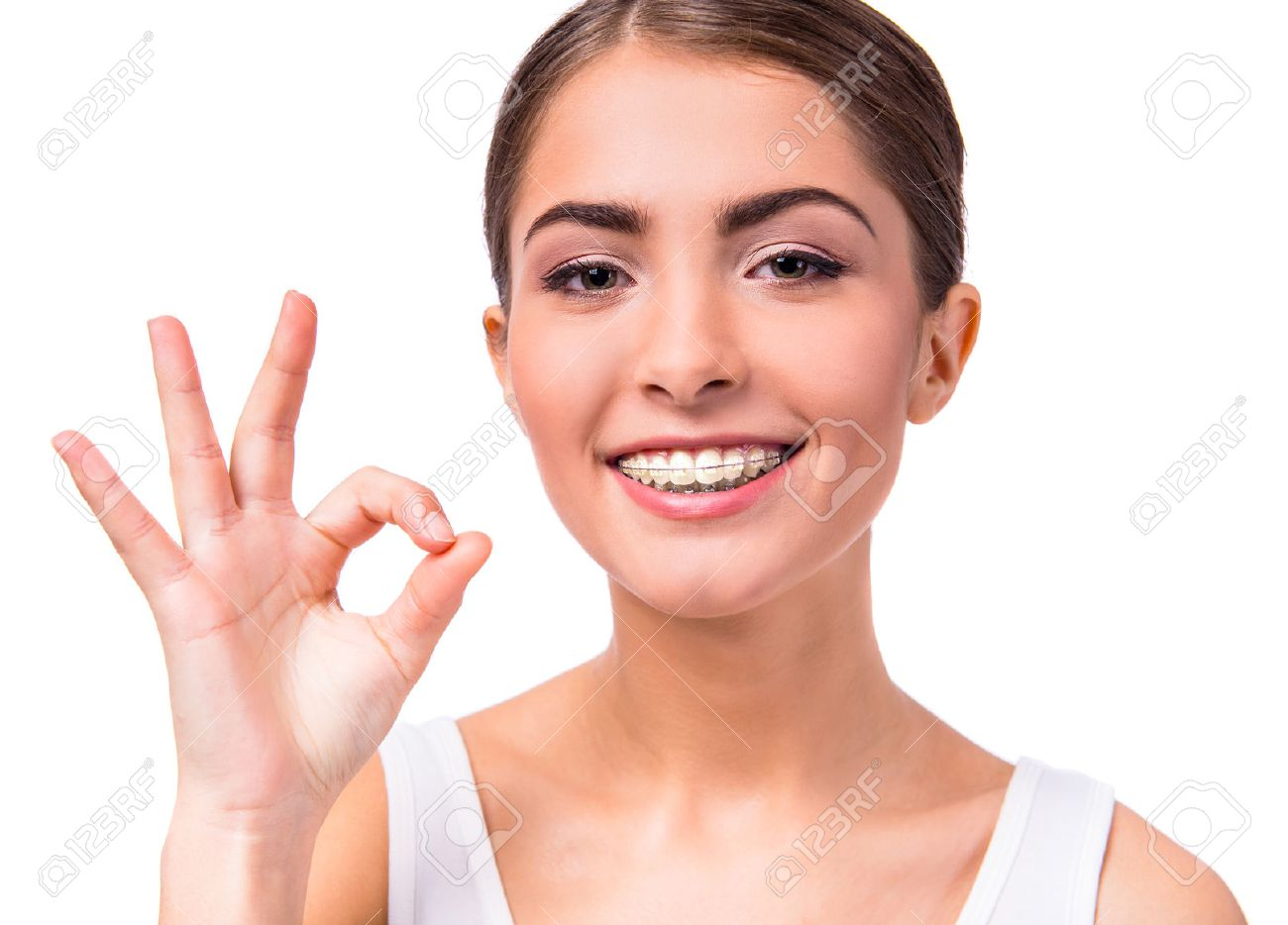 Portrait of a beautiful woman with braces on teeth, isolated on a white background Standard-Bild - 47179455