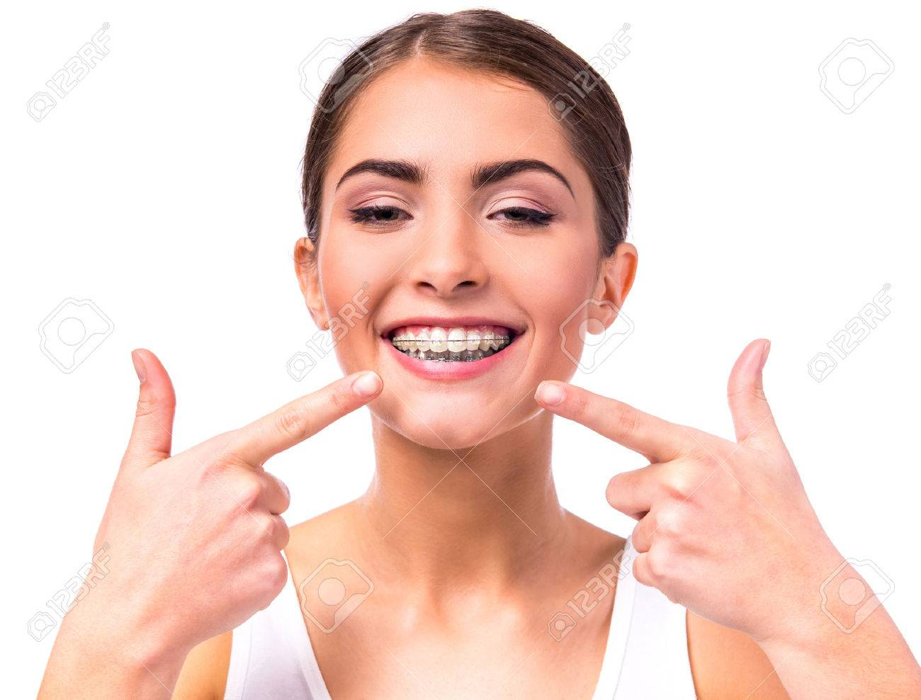 Portrait of a beautiful woman with braces on teeth, isolated on a white background Standard-Bild - 47178997