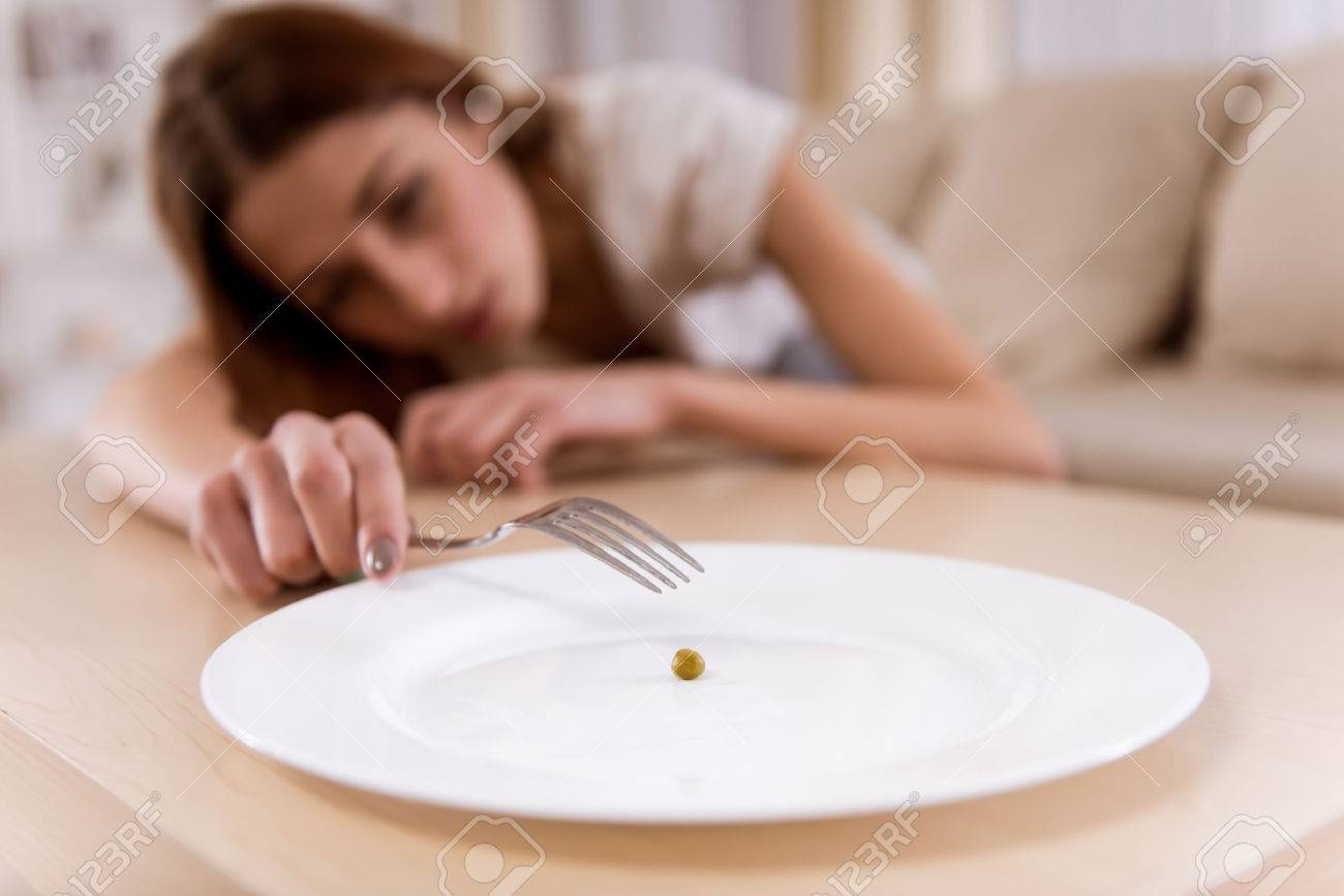 Girl exhausted from malnutrition lies on the sofa. Plate is empty side and closeup on the photo Standard-Bild - 51249422