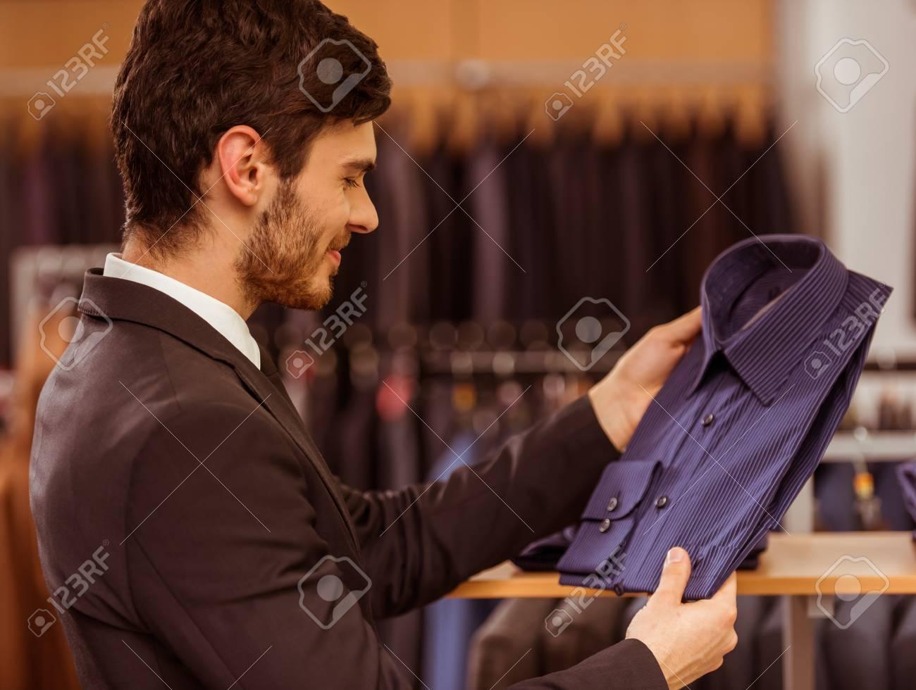 0d0ec1c3125 스톡 콘텐츠 - 현대 젊은 잘 생긴 사업가 찾고 양복 가게에서 고전적인 셔츠를 선택