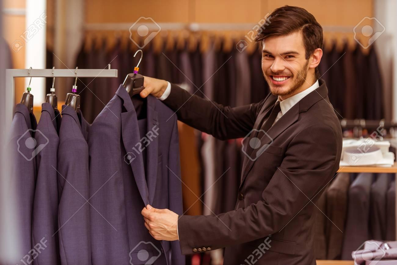 510b417d633 스톡 콘텐츠 - 현대 젊은 잘 생긴 사업가 웃고 찾고 양복 가게에서 클래식 정장을 선택
