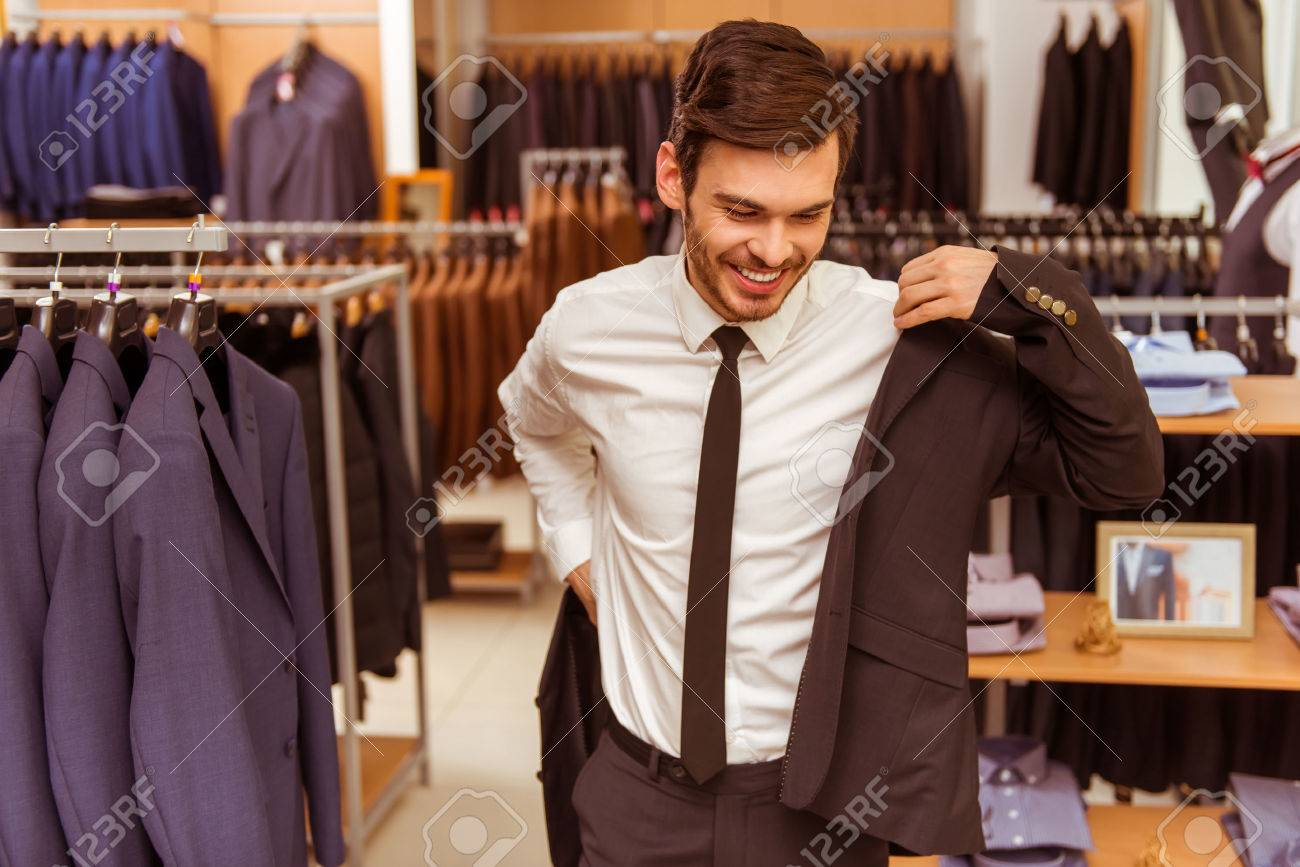 Modern young handsome businessman smiling and trying on classical suit in the suit shop Standard-Bild - 51687982