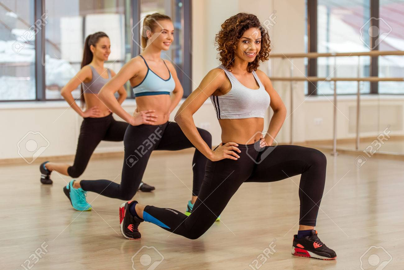 Three attractive sport girls smiling while doing lunges in fitness class. Beautiful Afro-American girl looking at camera Standard-Bild - 54005545