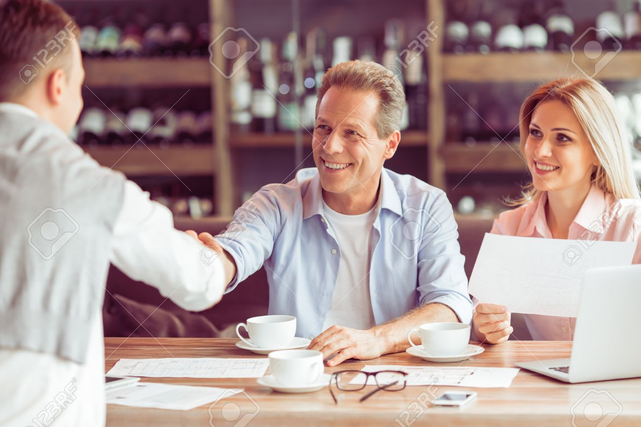 Business people are working during business lunch. Woman is holding a document, two men are handshaking Standard-Bild - 54005709