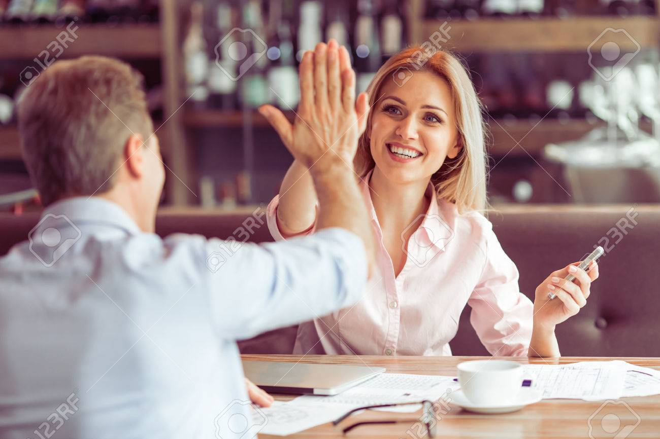 Beautiful business woman is giving high five and smiling to man during business meeting at the restaurant Standard-Bild - 54005744