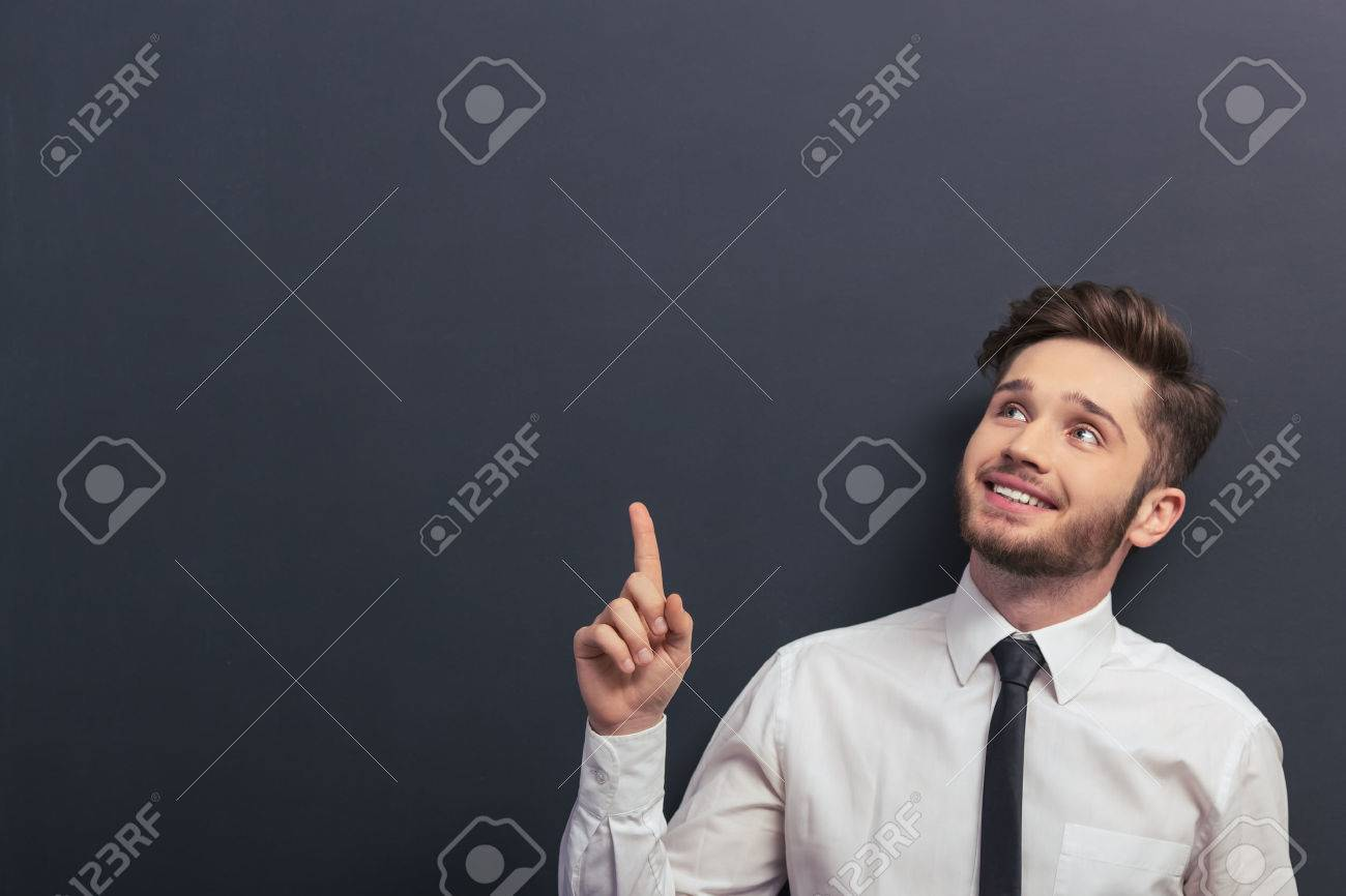 Handsome young student in white classic shirt is smiling, looking and pointing up, standing against blackboard Standard-Bild - 54005819