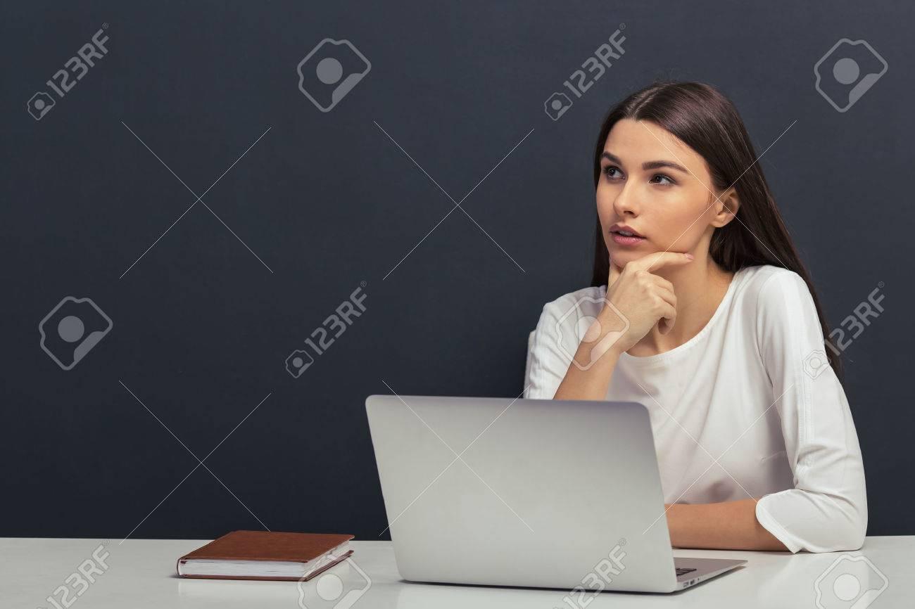 Nachdenklich schöne Student in der weißen Bluse hält Hand am Kinn und denken, an einem Tisch mit einem Laptop vor Tafel sitzen Standard-Bild - 54005831