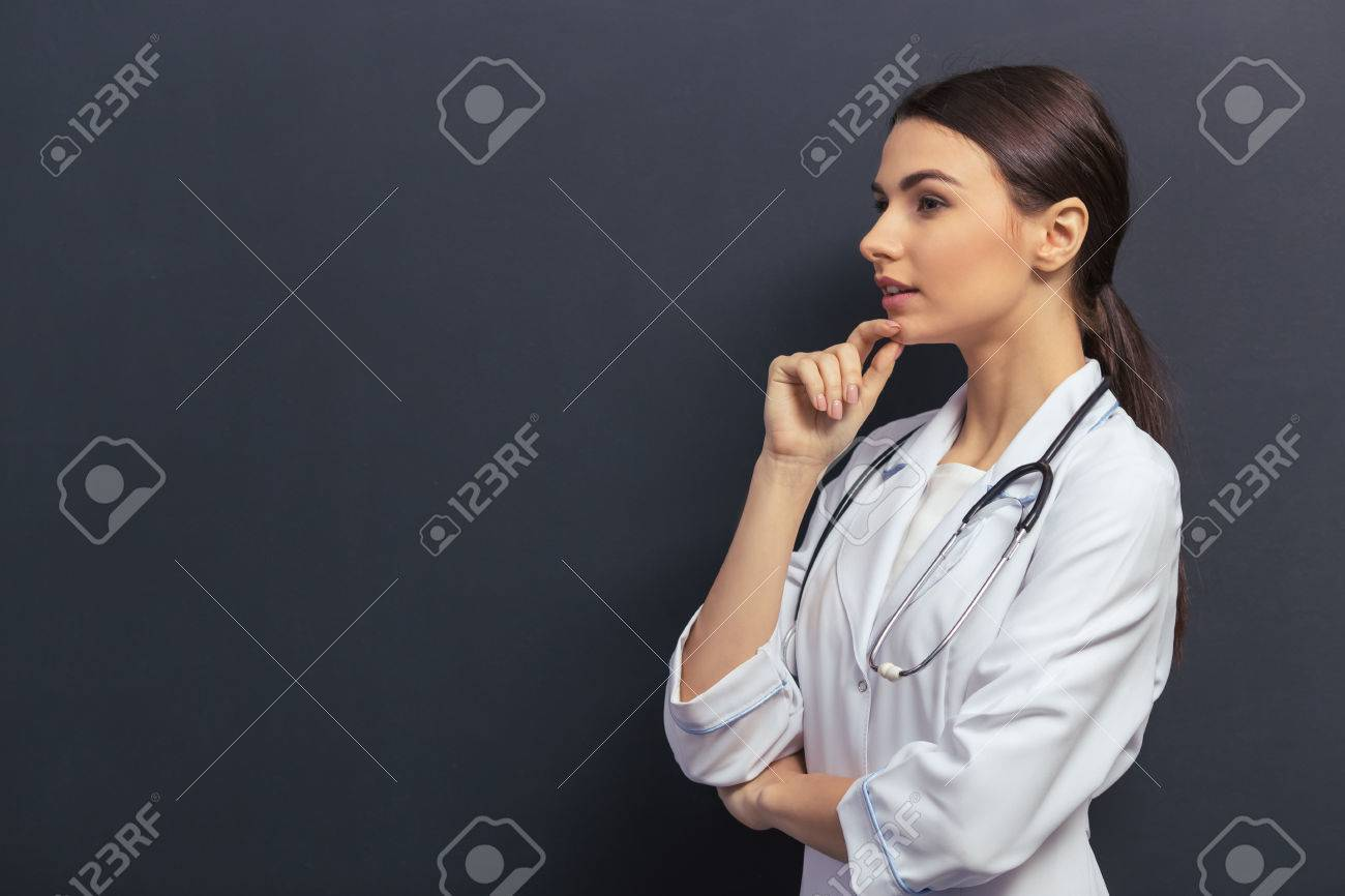 Side view of beautiful young doctor in white medical gown keeping hand on chin and thinking, against blackboard Standard-Bild - 54005882