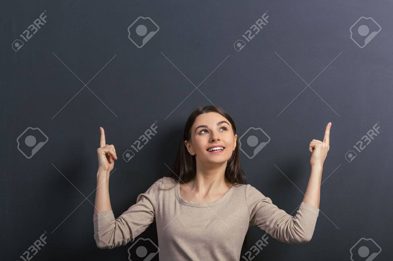 Beautiful young female student is smiling, looking and pointing up, standing against blackboard - 54005885