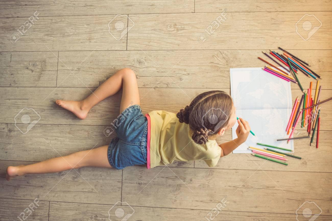 Vue De Dessus De La Charmante Petite Fille De Dessin En Utilisant Des Crayons Colorés En Position Couchée Sur Le Sol Dans Sa Chambre à La Maison