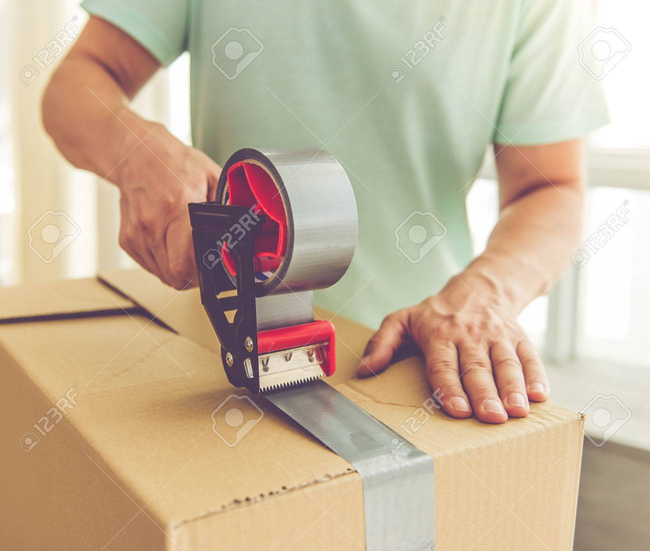 Cropped image of handsome mature man in casual clothes packing his stuff into the boxes using an adhesive tape while moving to the new apartment Standard-Bild - 63445866