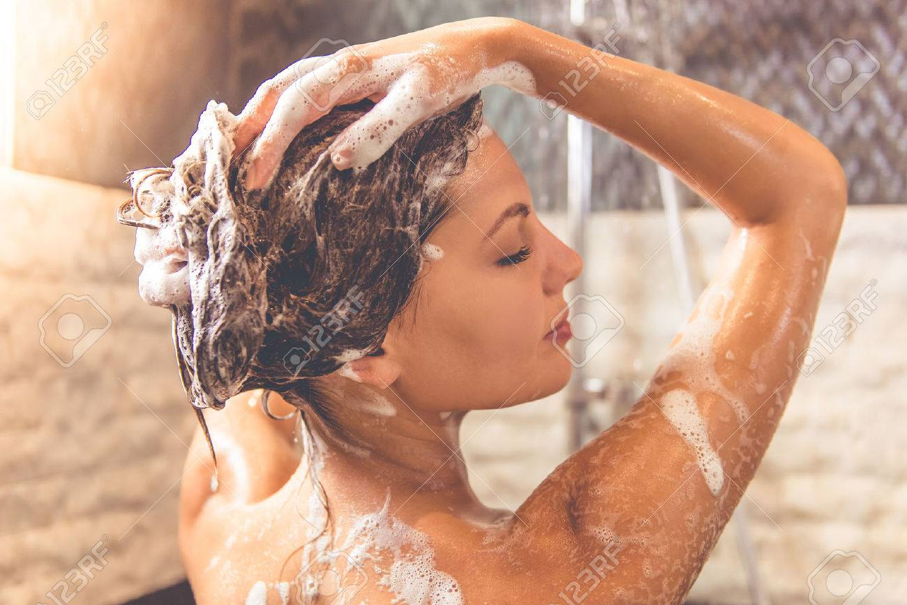Beautiful young woman is smiling and using shampoo while taking shower in bathroom Standard-Bild - 63891176