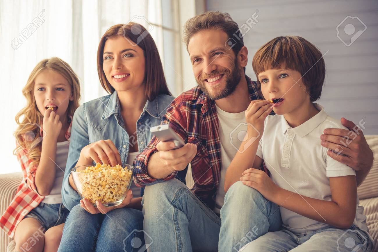 Beautiful young parents and their children are watching TV, eating popcorn and smiling while sitting on couch at home Standard-Bild - 63889309