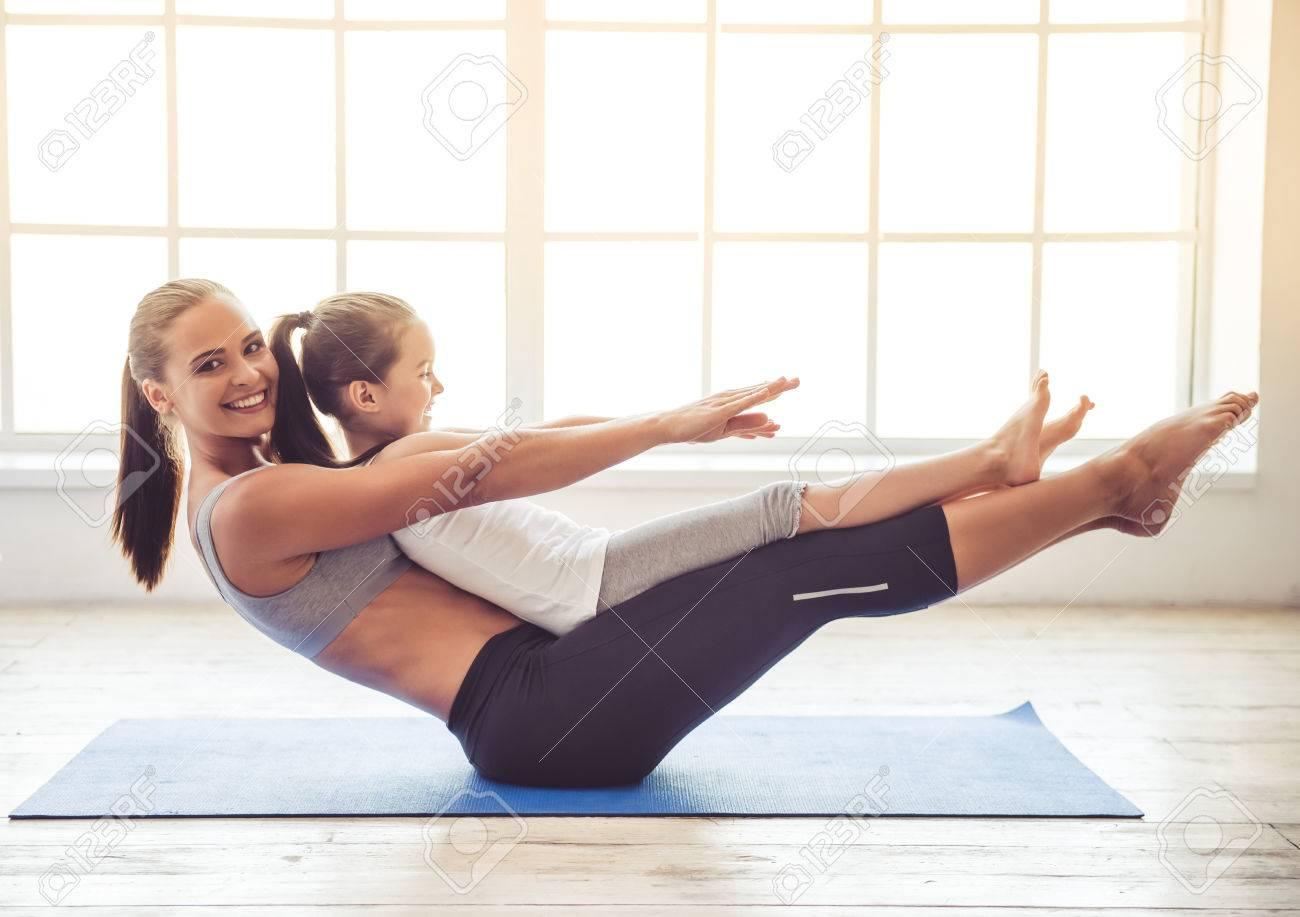 Schöne junge Frau und charmantes kleines Mädchen lächeln, während Yoga in Fitness-Saal tun zusammen Standard-Bild - 63888759