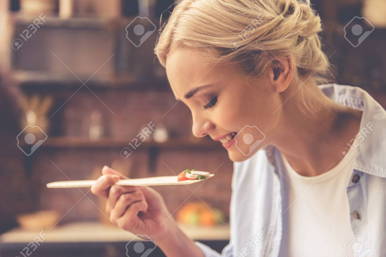 Beautiful girl is tasting food and smiling while cooking in kitchen at home Standard-Bild - 65420486