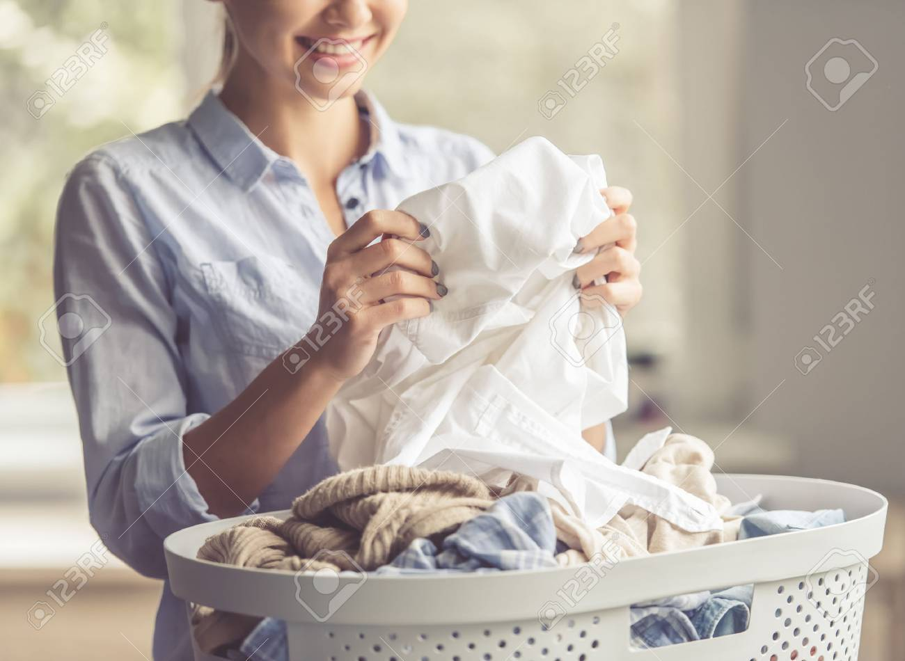Cropped image of beautiful young woman is smiling while doing laundry at home Standard-Bild - 65422817