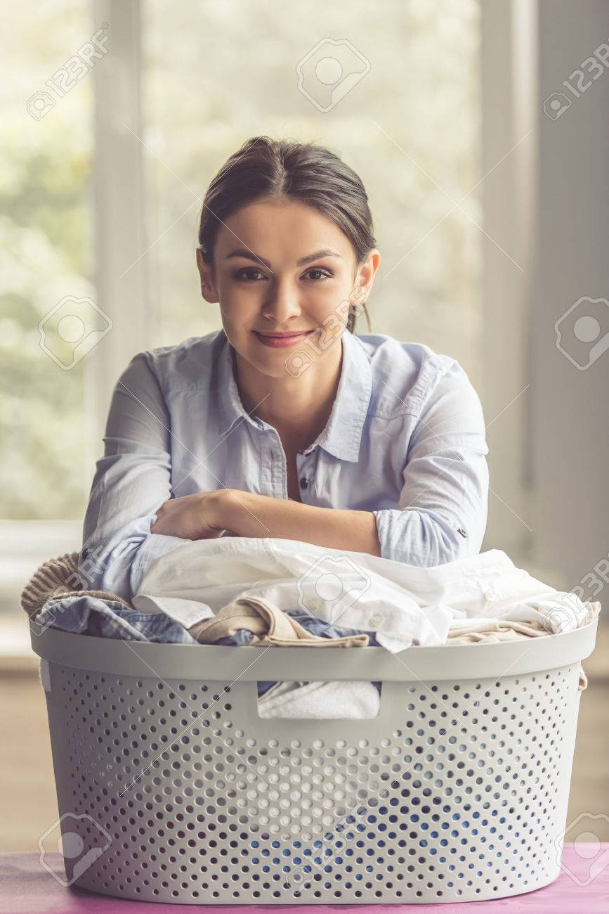 Beautiful young woman is leaning on the basin with laundry, looking at camera and smiling Standard-Bild - 65423106