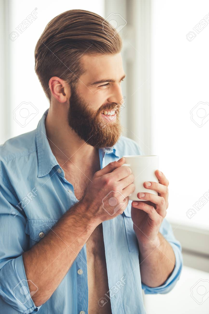 2afd5bbe7260 Archivio Fotografico - Uomo bello con barba in camicia sbottonata è in  possesso di una tazza e sorridente