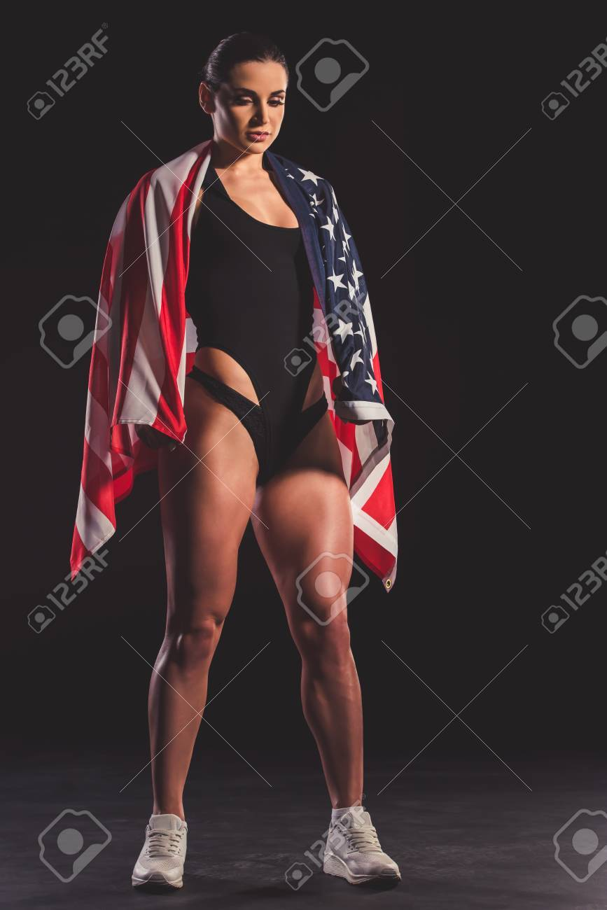 Full length portrait of beautiful strong muscular woman with American flag  on dark background Stock Photo 09cd2d894