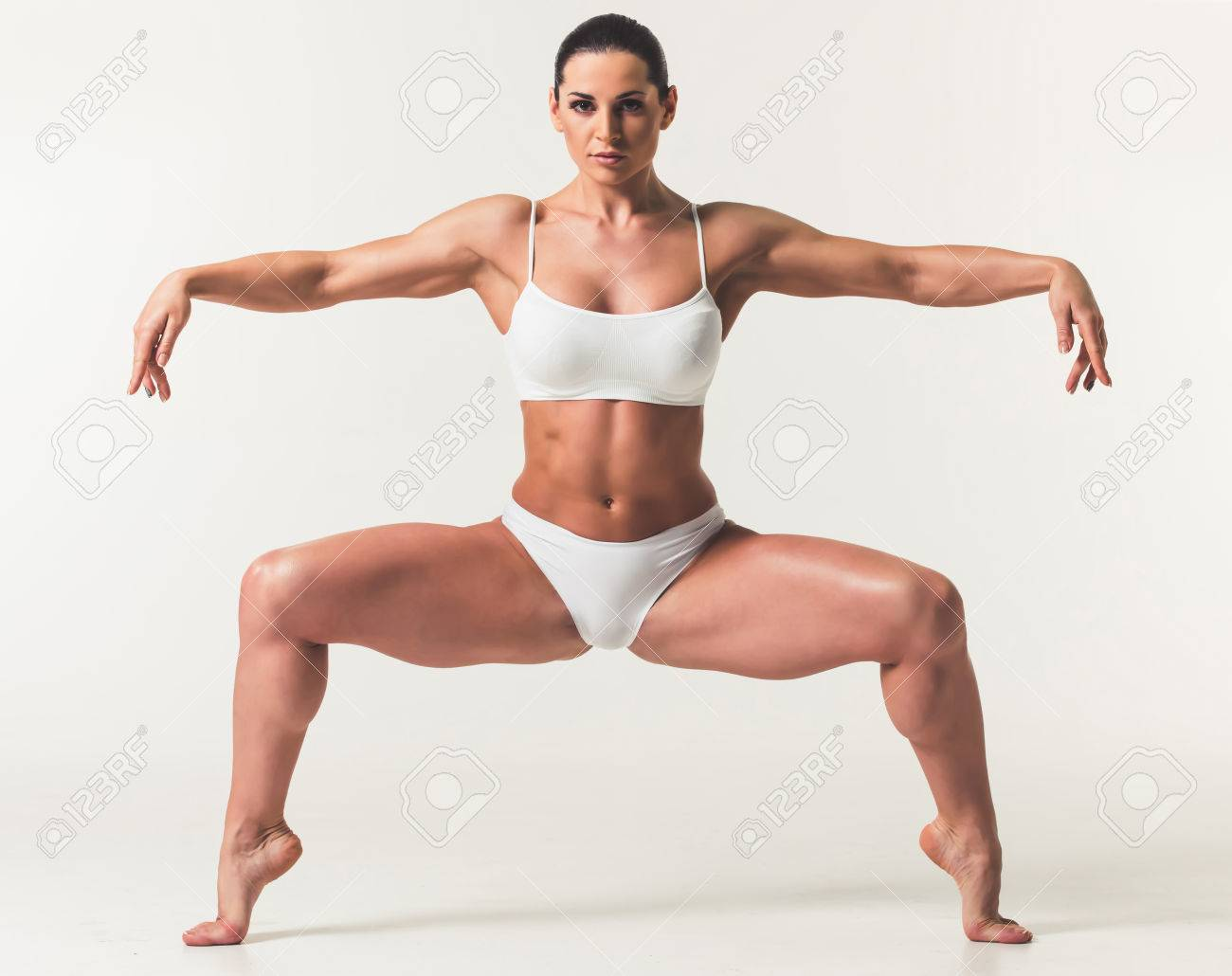 Beautiful strong woman in white underwear performing plie on light background  Stock Photo - 73416112 e533ad925