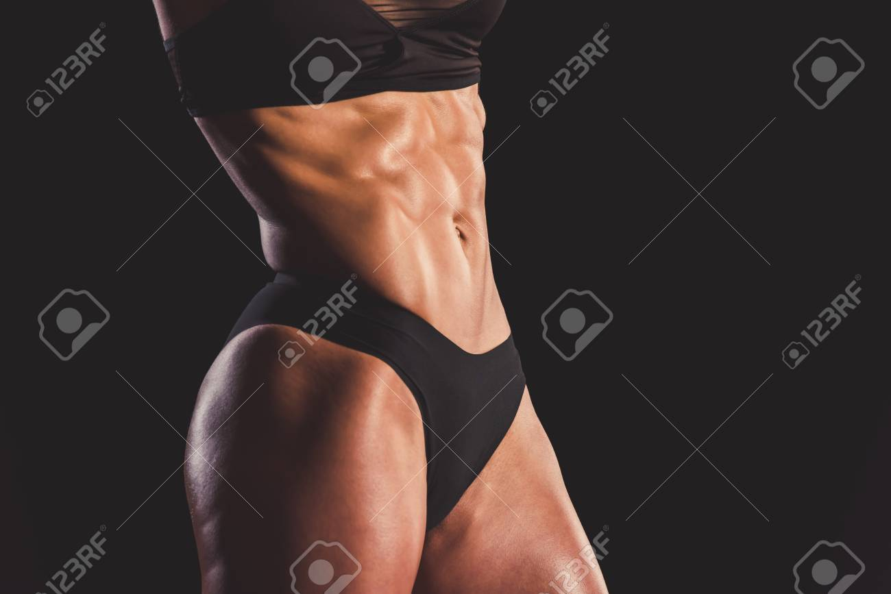 Cropped image of beautiful strong woman in black underwear showing her  abdominal muscles 87b86434b