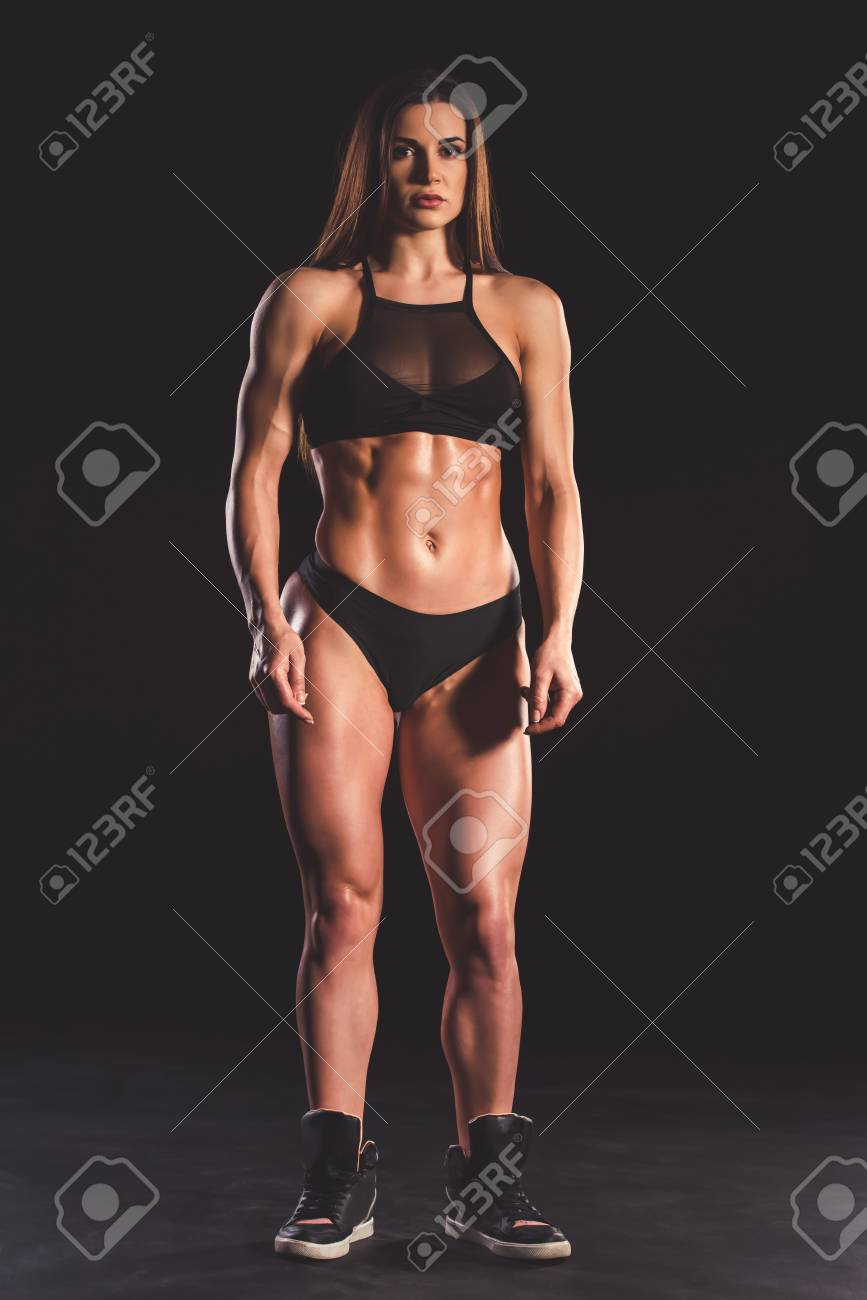 Full length portrait of beautiful strong muscular woman in black underwear  on dark background Stock Photo 032824362