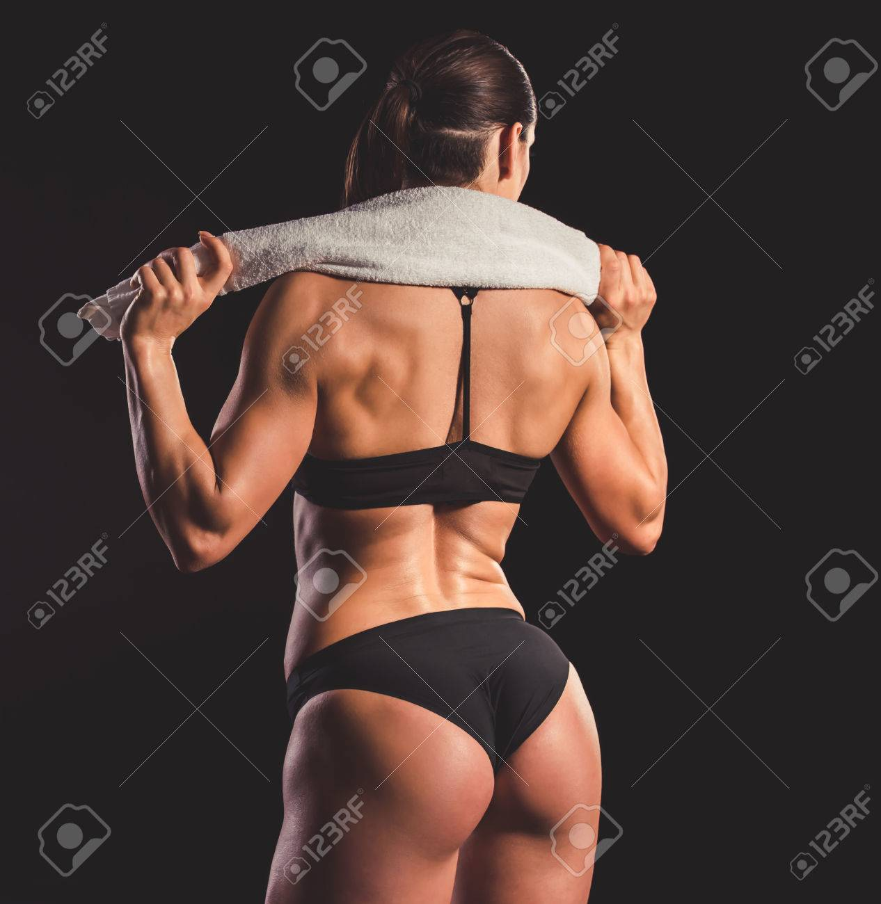 Back view of beautiful strong muscular woman in black underwear holding a  towel 495b83698