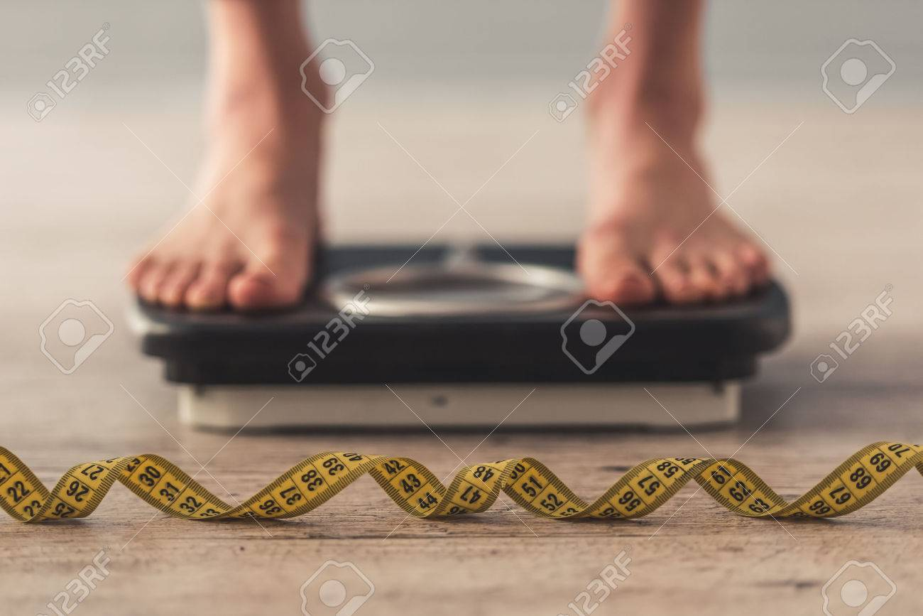 Cropped image of woman feet standing on weigh scales, on gray background. A tape measure in the foreground - 74490207