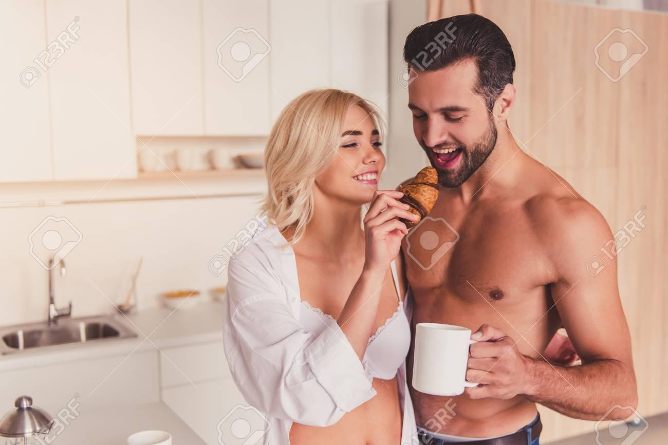 Hermosa Joven Semi Desnuda Pareja Es Comer Croissants Beber Café Y Sonriente Mientras Que Un Desayuno En La Cocina Por La Mañana