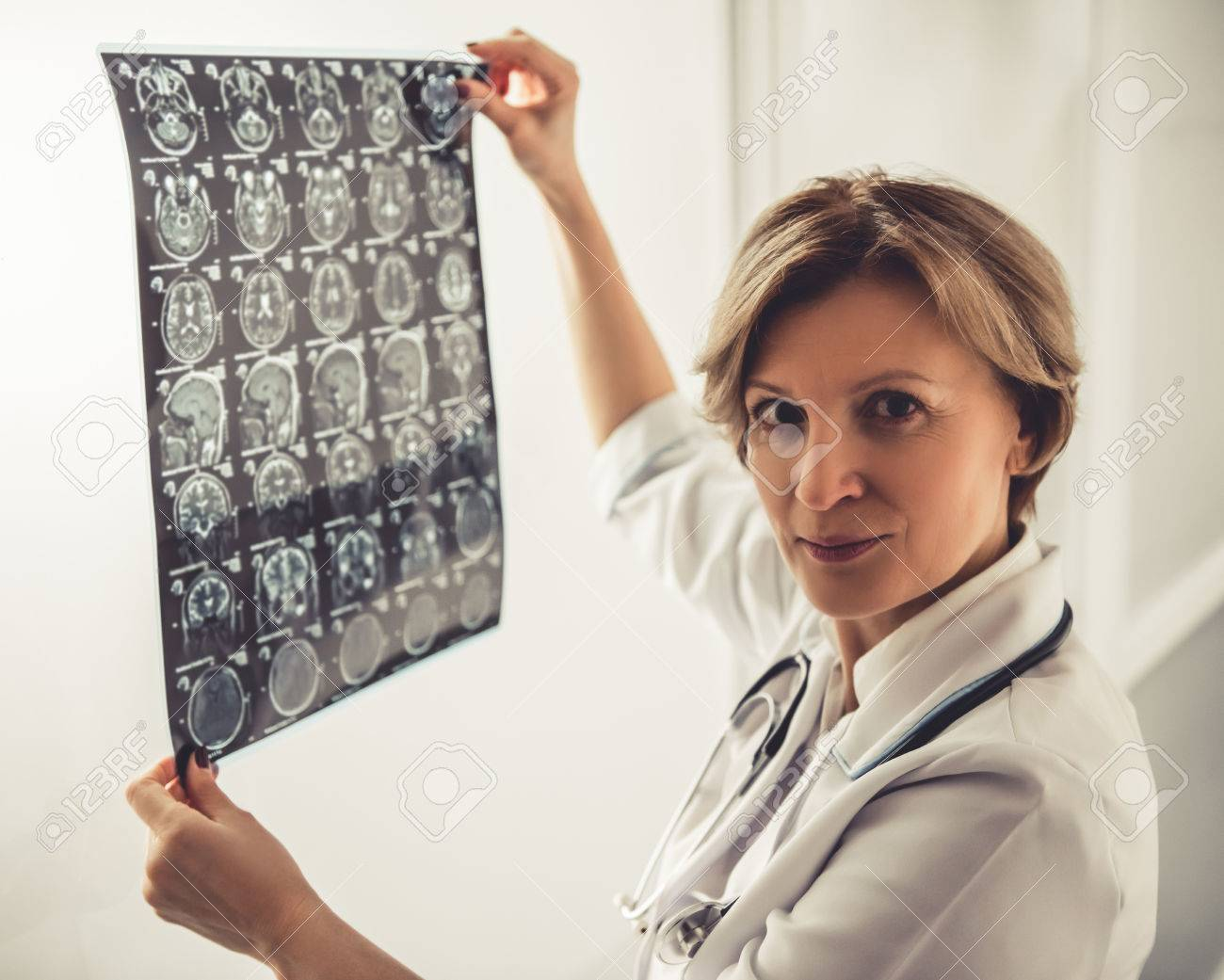 beautiful mature doctor in white coat is holding x ray image.. stock