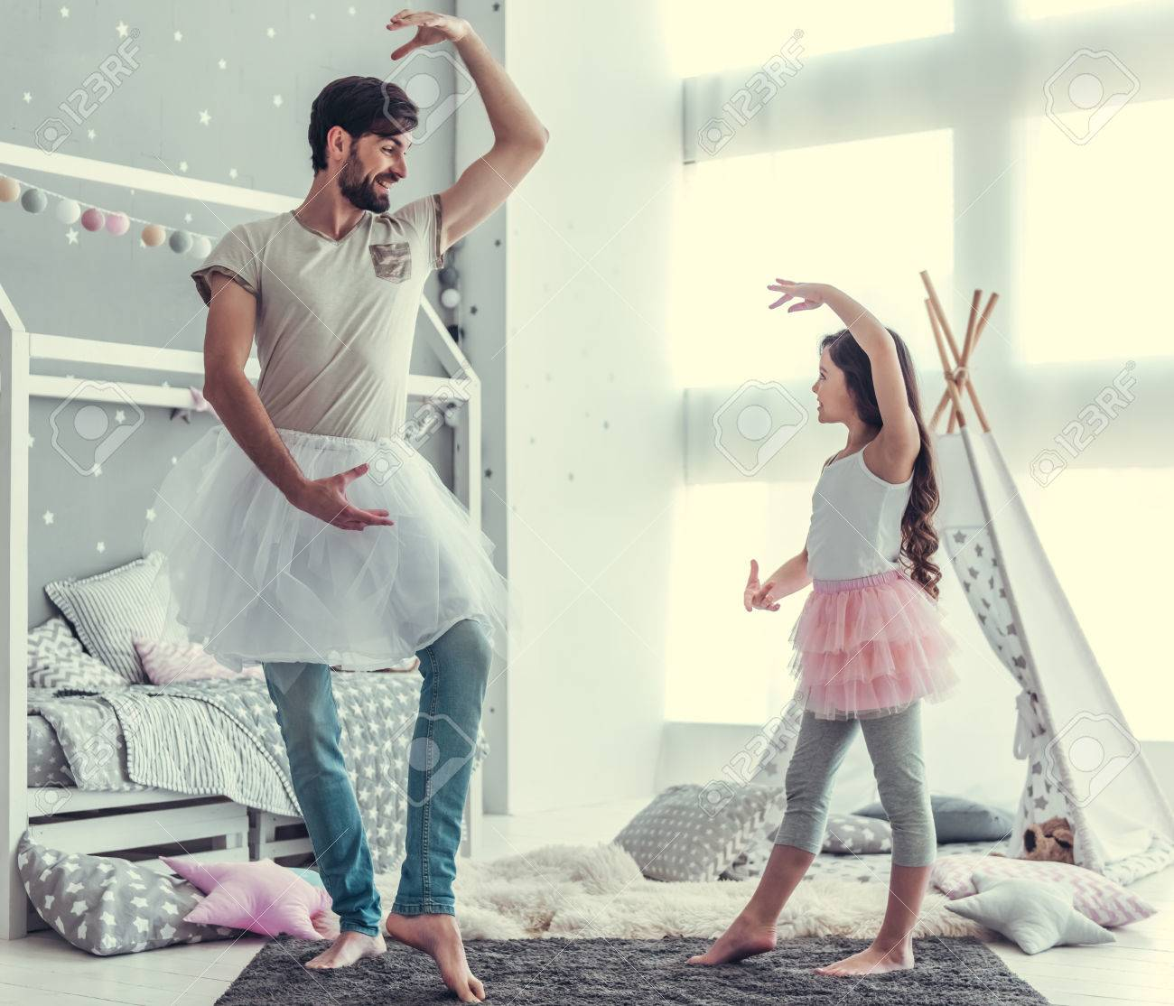 Cute little daughter and her handsome young dad in skirts are dancing and smiling while playing together in child's room Standard-Bild - 81786730