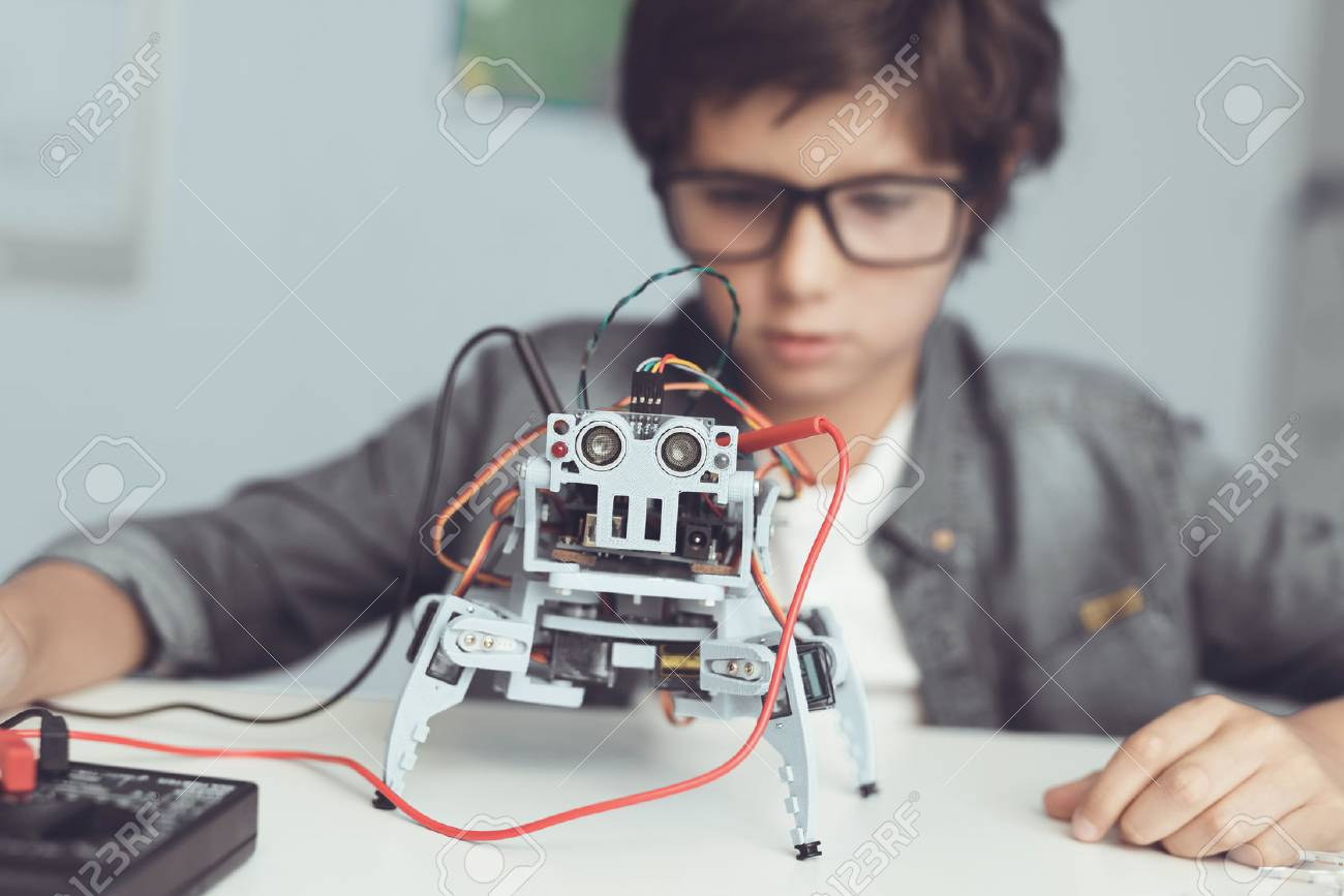 A small nerd in glasses is holding a robot. He looks carefully at his creation - 90223784