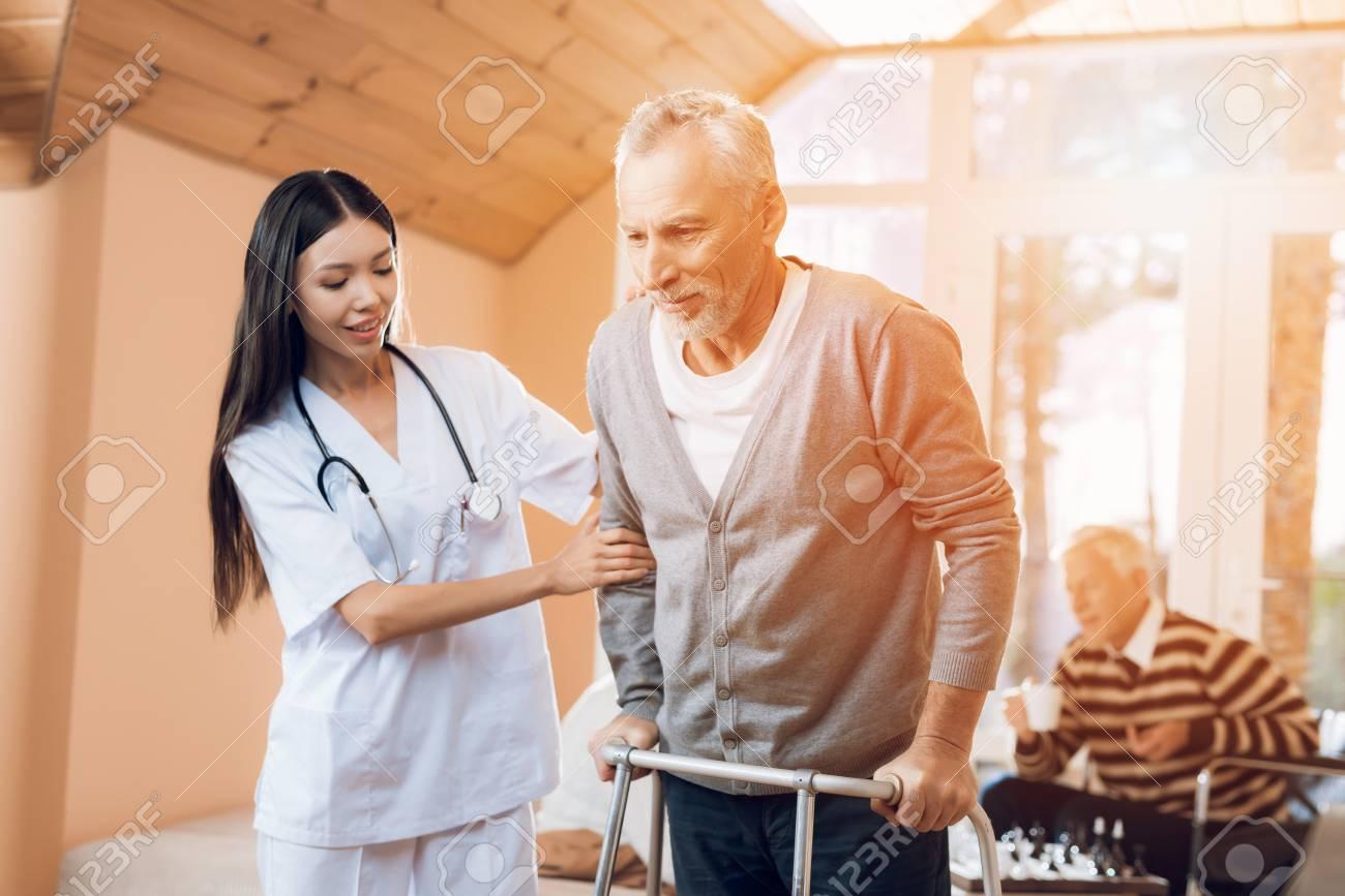 An asian nurse helps a man on an adult walker in a nursing home. - 91434633
