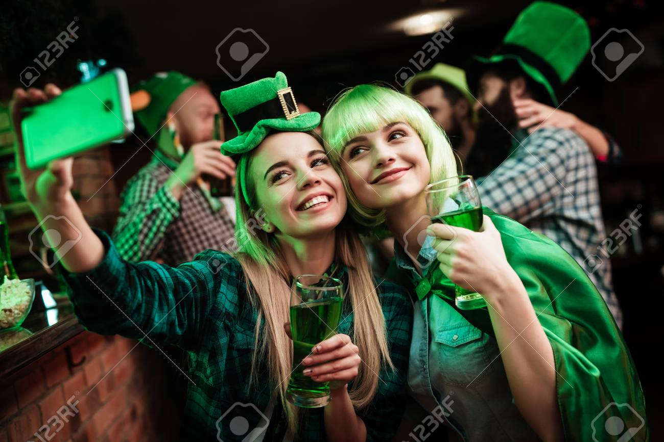 Two girls in a wig and hat make selfi at the bar. - 93688506