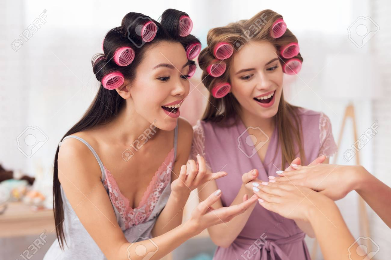 Three girls with curlers in their hair showing nail polish. They are celebrating womens day March 8. - 95803871
