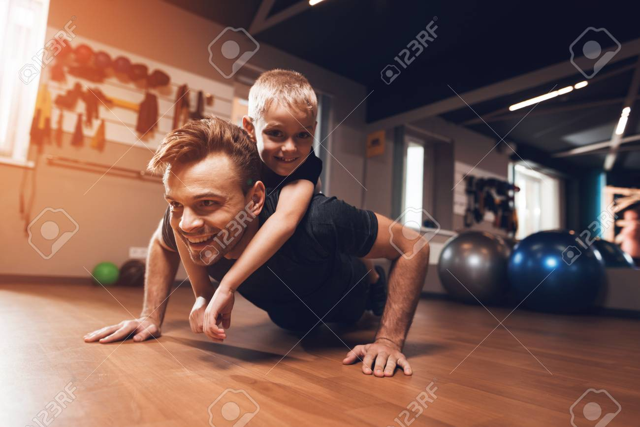 Father and son in the gym. Father and son spend time together and lead a healthy lifestyle. Man and boy are working out. Father and son are doing exercise. - 96221516
