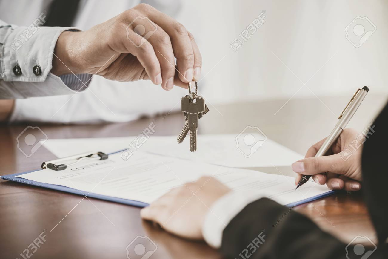 Young woman is signing financial contract with male realtor. Close-up. - 97440342
