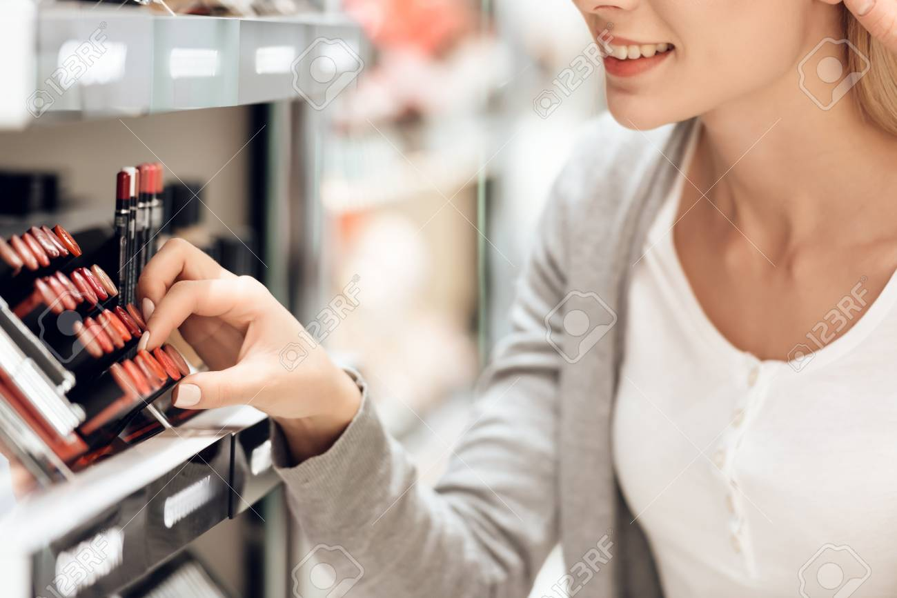 Blonde buys lipstick in cosmetics store. Shopping concept. - 100928521