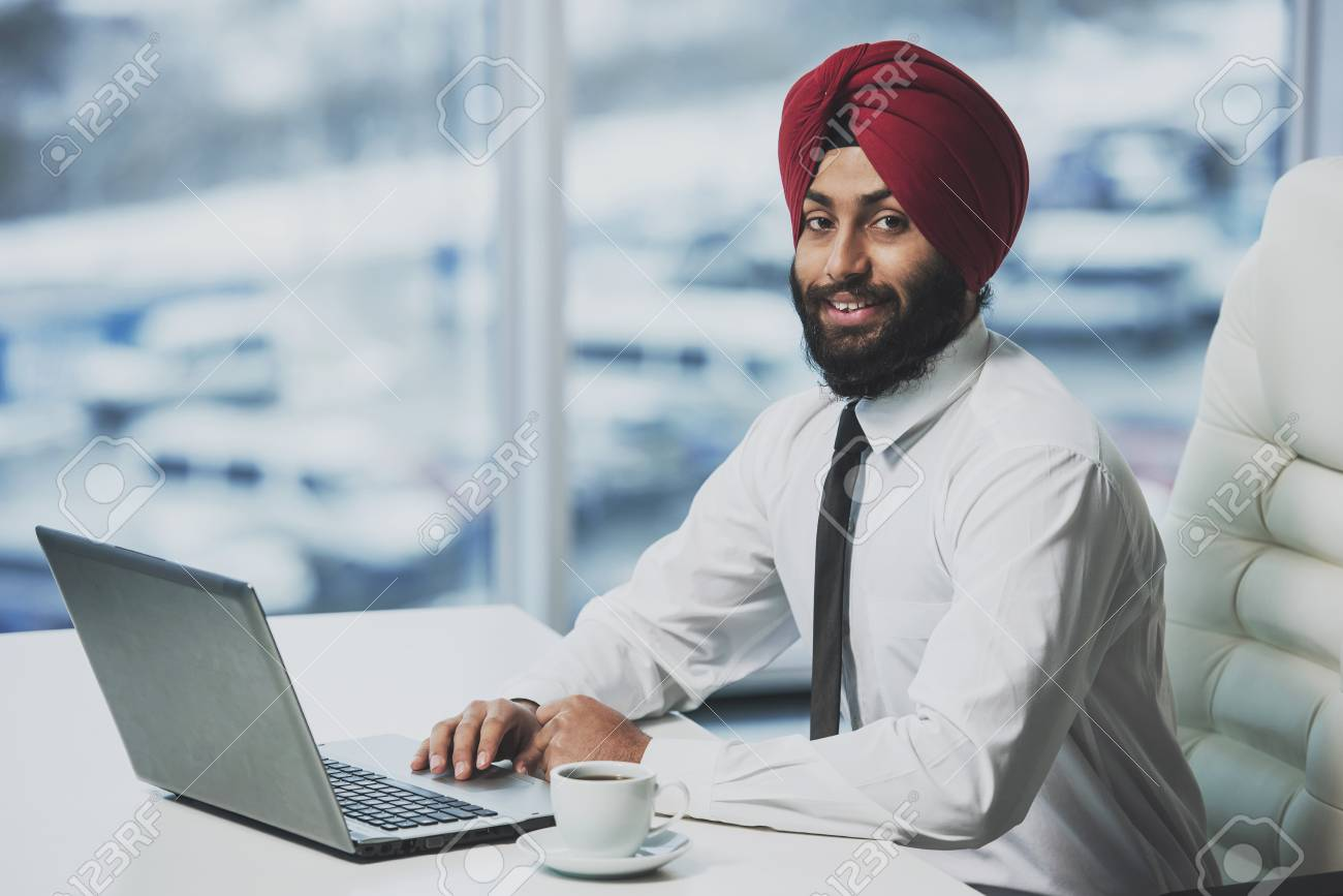 Young indian bearded businessman working behind laptop in modern office. Business people. - 102947120