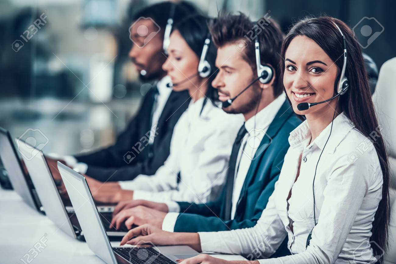 Multicultural young happy employees in call center sitting at computers and working. Teamwork. Employees in headset. - 102994432