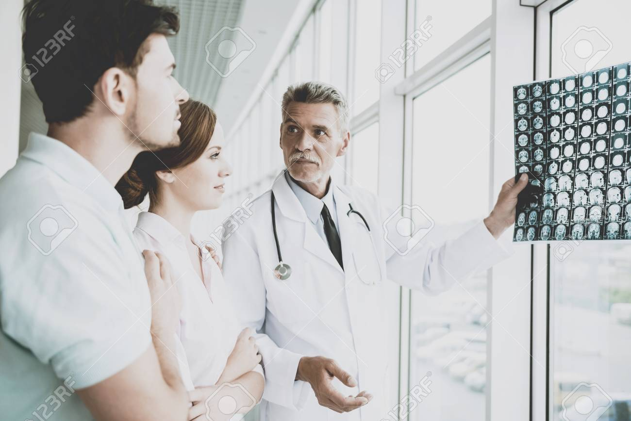 Tense Male Doctor Indicates on Image of Roentgen. Showing Patients Results at Diagnostic Centre. Rapid Improvement. Doctors and Patients Discuss in Clinic. Professional in Coat with Stethoscopes. - 104541558