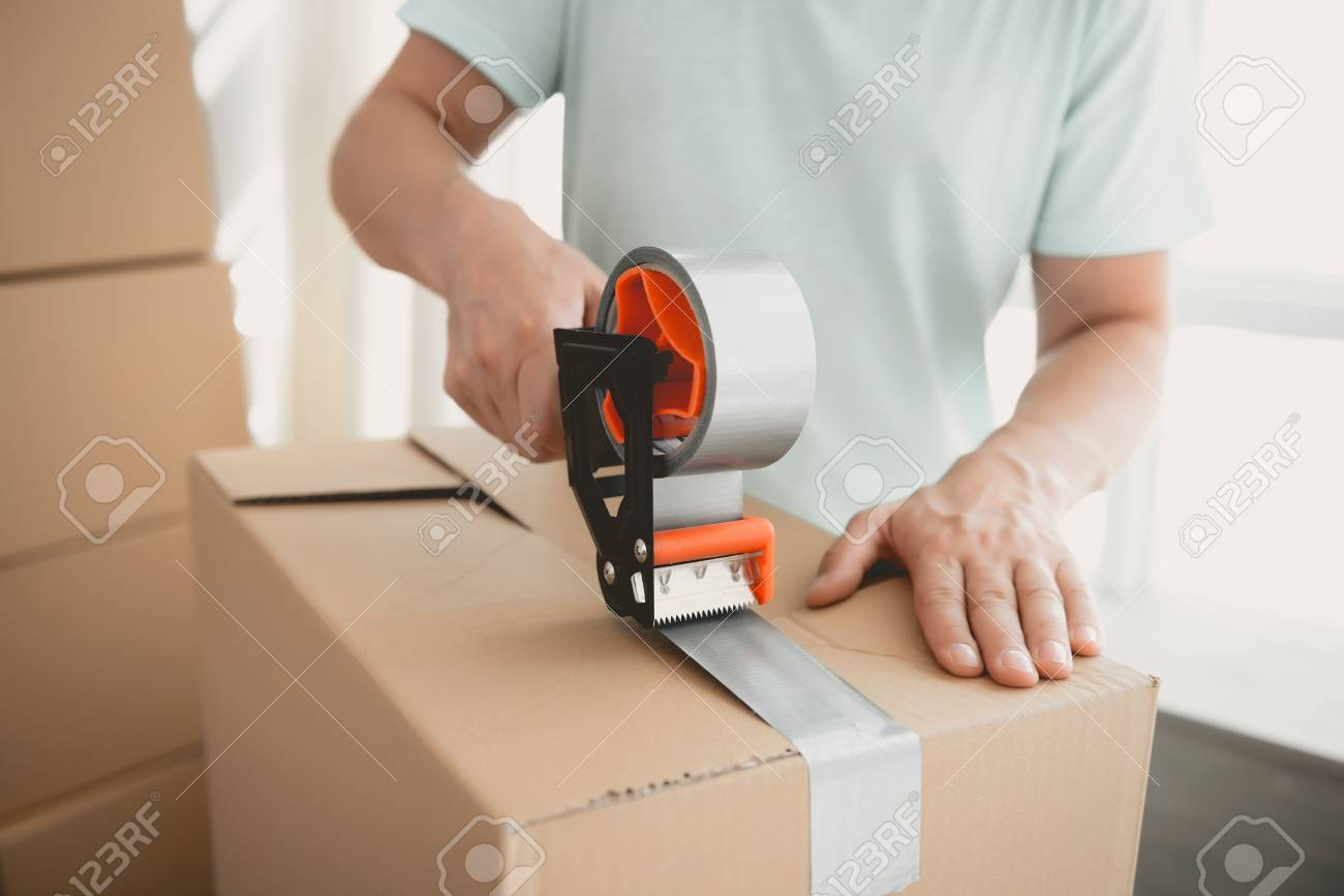 Close up. Packing Boxes with Building Tape in Order to Move to New Housing. Moving the Family to New Place. Family Gathers Things in Cardboard Boxes. Young Man in Room. New Apartment Concepts. - 105986034