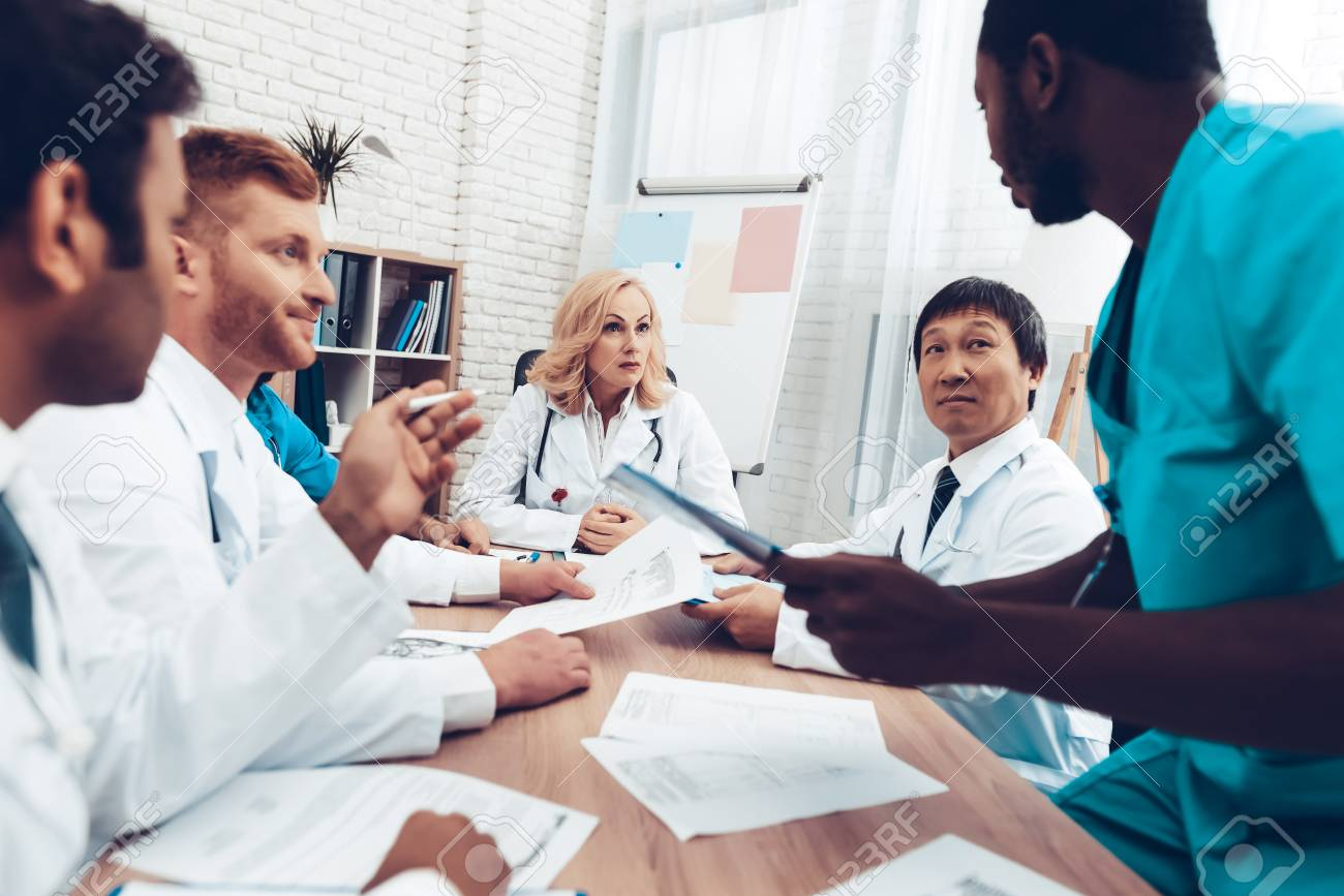 Doctors Meeting. Diagnostic Discussion. Multinational Medicals. Professional Consultation. Patient's Test Results. Young Specialists. Clinician Team Group. Physician Assistants. Sitting Interns. - 105914697