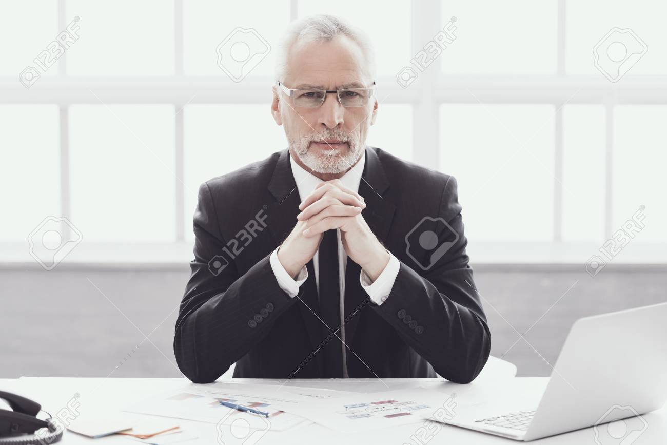 Businessman at Work in Office. Corporate Lifestyle. Professional Mature Bearded Worker Sitting at Desk next to Laptop. Successful Confident Businessman wearing Suit and Glasses at Work. - 107271715