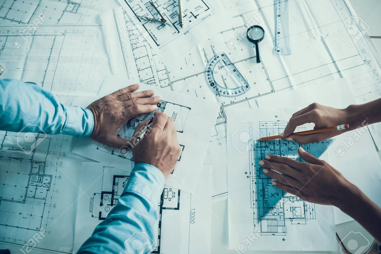 Closeup of hands of architects Drawing Blueprint. Two Creative Colleagues Designing Plan of new Building Together in Office. Business Corporate People Working Together. Team work Concept - 107272200