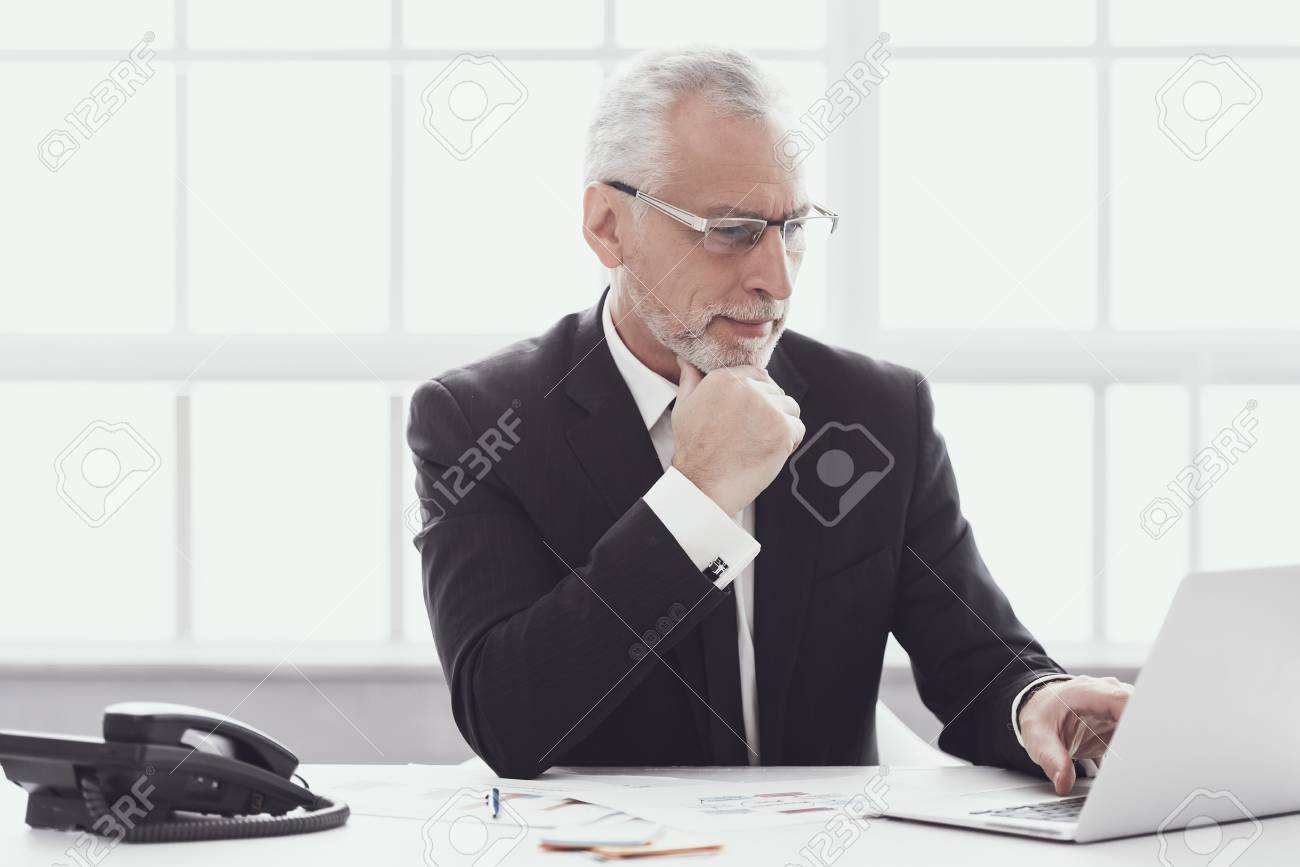 Adult Businessman Working on Laptop in Office. Professional Mature Bearded Worker Sitting at Desk and Working on Computer. Successful Businessman wearing Suit at Work. Corporate Lifestyle Concept - 107272205