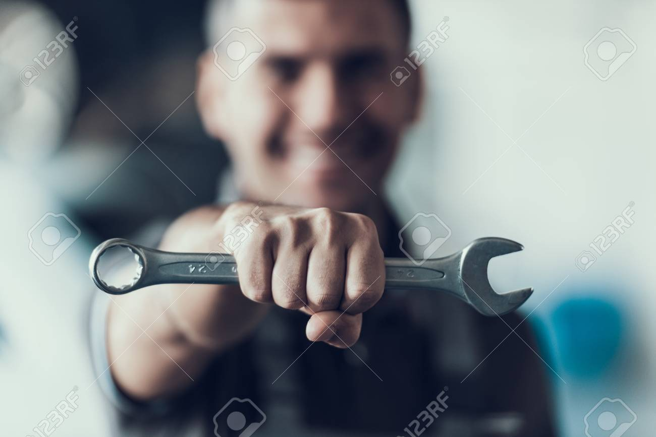 Auto Mechanic with Tool on Blurred Background. Close-up of Repairman Strong Fist Holding Metalic Wrench in Garage. Automobile Repair Service Concept. Automobile Master Concept - 107286973
