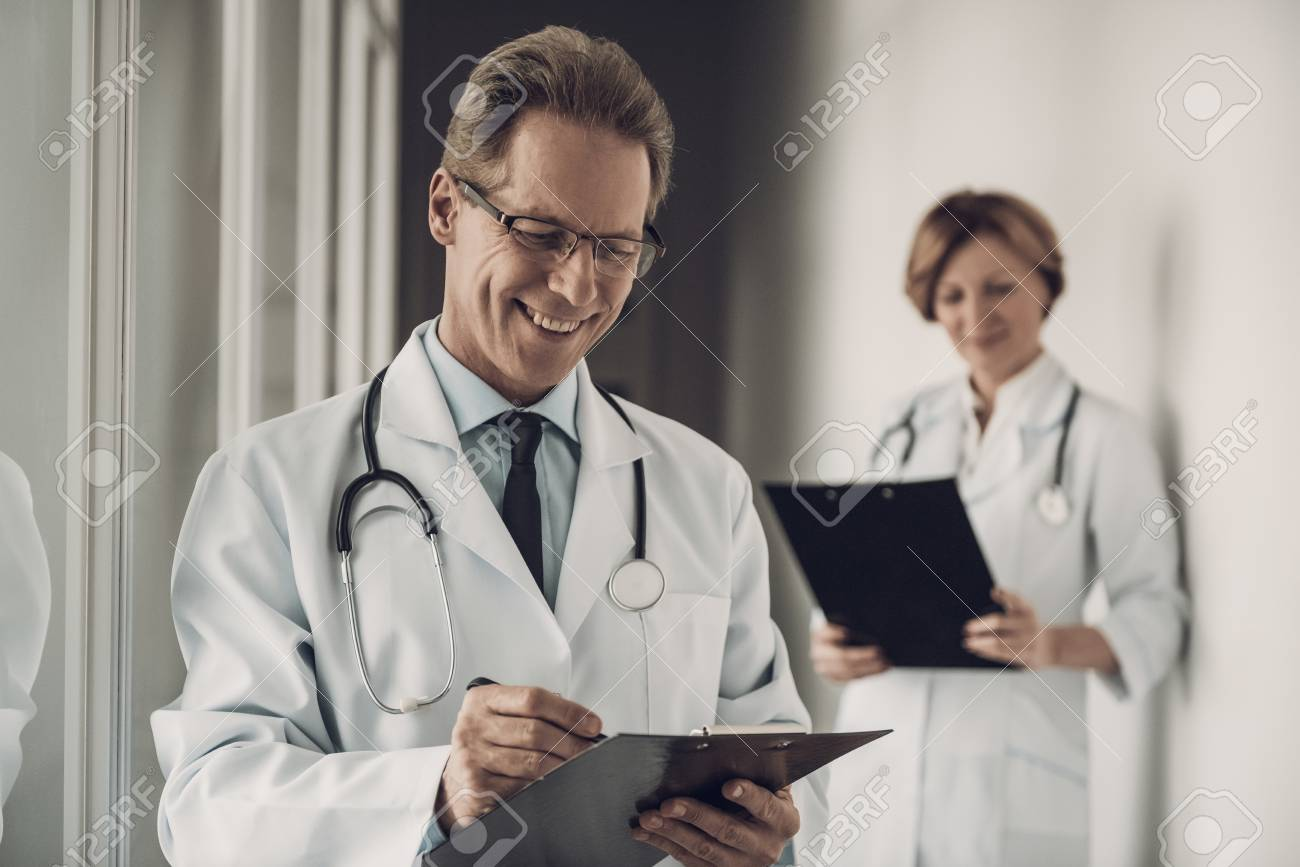 Doctor and Nurse Filling up Medical History. Portrait of Caucasian Experienced Medicine Attractive Workers in Uniform Making Diagnosis Standing in Hospital. Healthcare Concept - 107349459