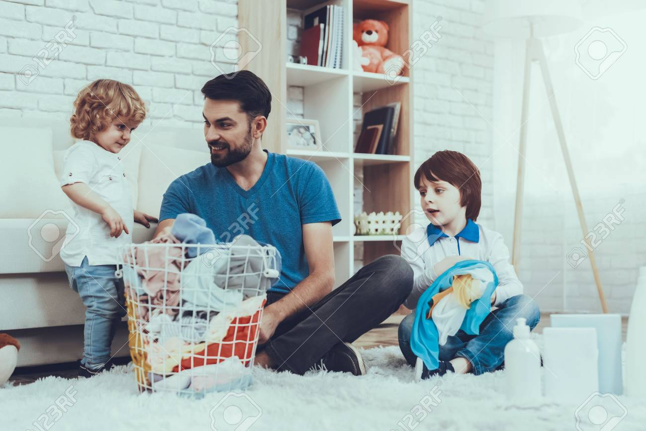 Two Boys. Help Wash Clothes. Father. Baby with Bright Hair. Smiling Kids. Spends Time. Happy Together. Leisure Time. Man. Smile. Home Time. Family. Holidays. Father Two Boys. Dirty Laundry. Basket. - 108915339