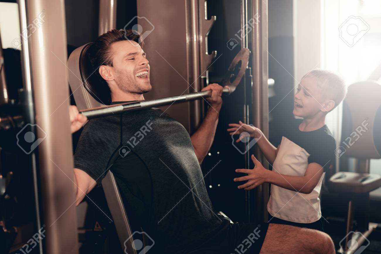 Son Support To Father While Lifting The Barbell. Parenthood Relationship. Sporty Family Concept. Active Lifestyle. Happy Childhood. Holiday Leisure. Working Out Together. Fitness Day. - 109559343